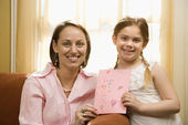 Girl giving mom drawing. — Stock Photo