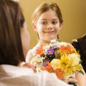 Girl giving mom flowers. — Stock Photo