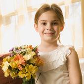 Girl holding flowers. — Stock Photo