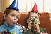 Children blowing noisemakers. — Stock Photo