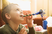 Boy blowing noisemaker. — Stock Photo