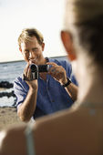 Smiling Man Filming Woman At Beach — Stock Photo