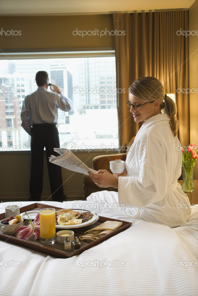 Caucasian woman in a robe sits on a hotel bed while reading the newspaper. A man stands in the background talking on his mobile phone. Vertical shot. — Stock Photo #9550314