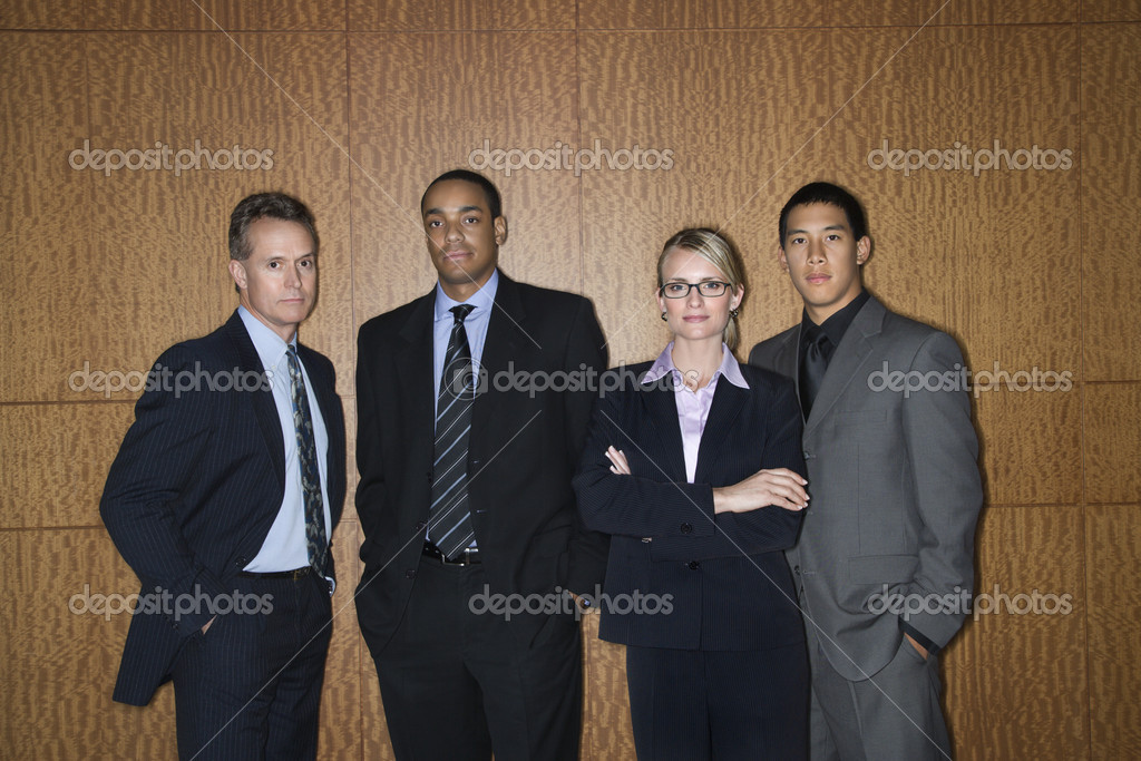 Ethnically diverse businessmen and a businesswoman stand in a lineup as they look towards the camera. Horizontal shot.  Stock Photo #9550337