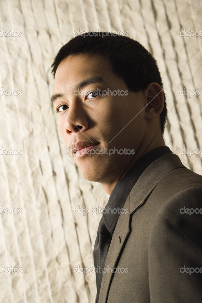 Low angle head-and-shoulders portrait of Asian young adult businessman. Vertical format. — Photo #9550532