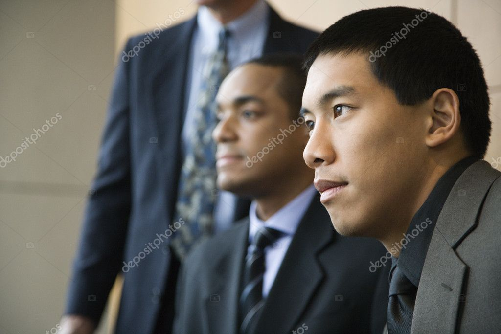 Asian businessman in the foreground with African-American businessman and a third businessman in the background. Horizontal format. — Stock Photo #9550557