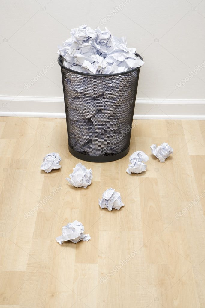 Full wire mesh trash can with crumpled paper scattered around. — Stock Photo #9550920