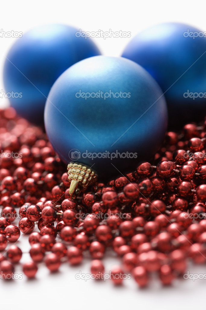 Still life of large blue Christmas ornaments and strings of red beads.  Stock Photo #9551617