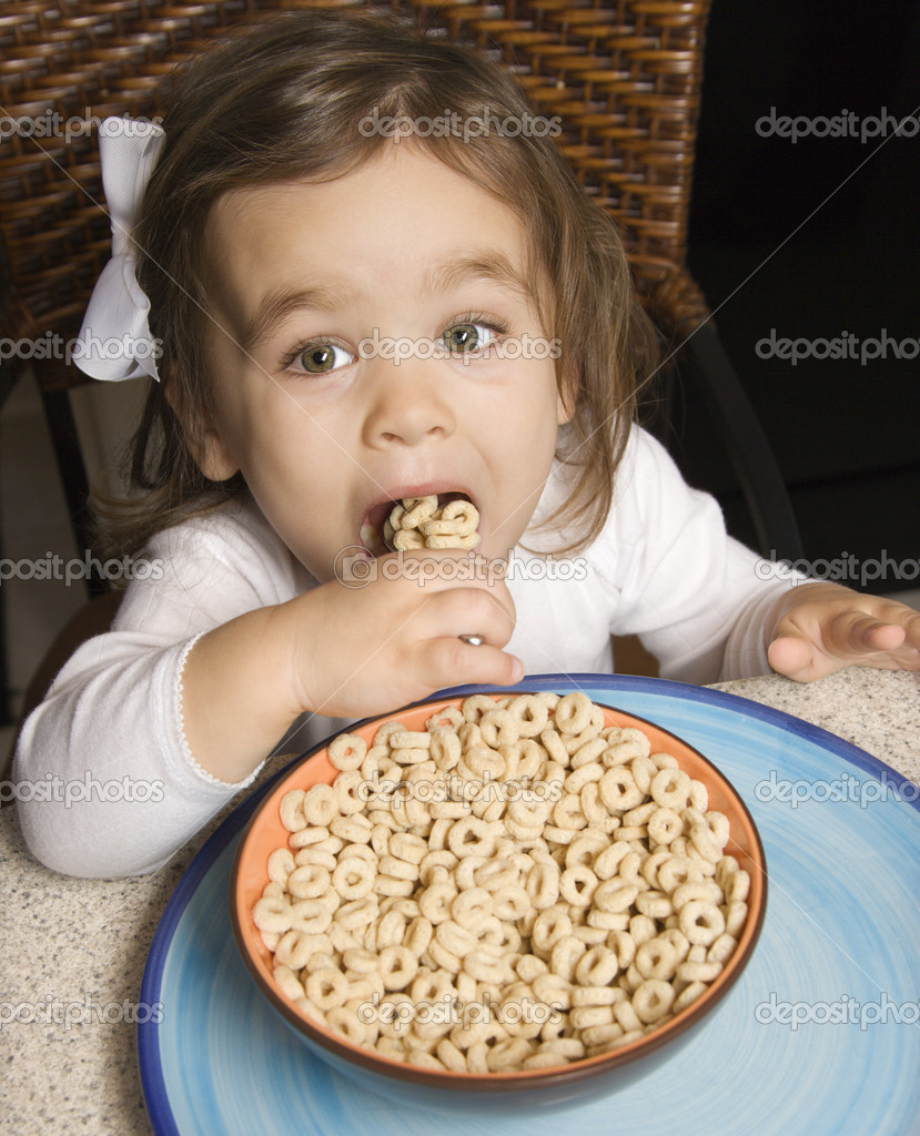 Caucasian girl eating bowl of cereal.  Stock Photo #9551722
