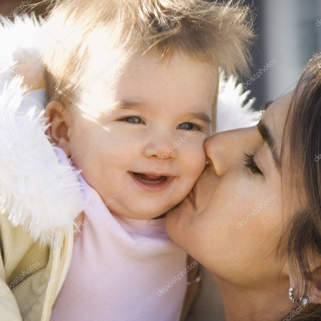 Caucasian mother holding and kissing smiling baby girl.  Stock Photo #9551868
