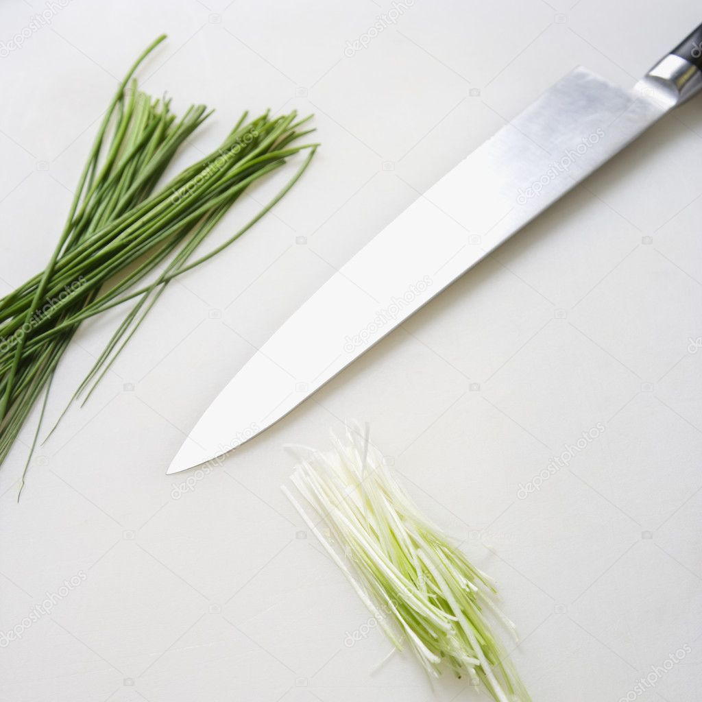 Fresh chives with kitchen knife resting on countertop. — Stock Photo #9551881