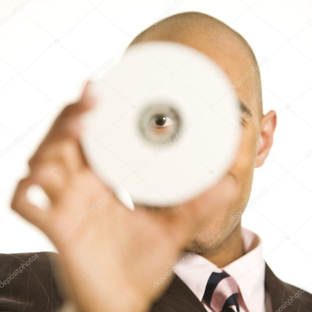 African American man holding compact disc over face and peeking through hole. — Stock Photo #9552419