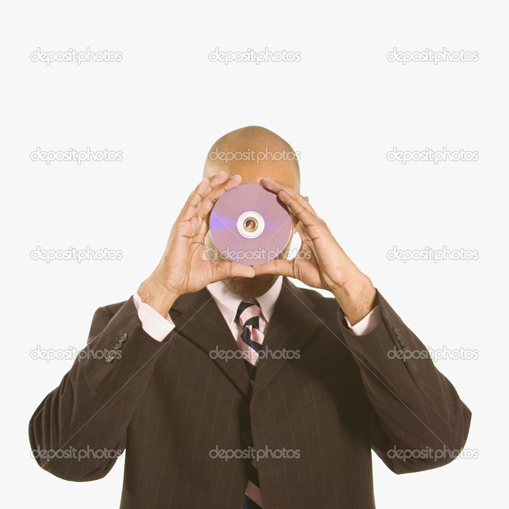 African American man holding compact disc over his face.  Stock Photo #9552434
