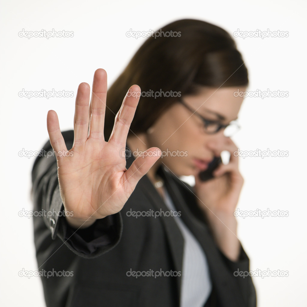 Caucasian mid adult professional business woman talking on cell phone holding hand out to stop viewer. — Stock Photo #9552528