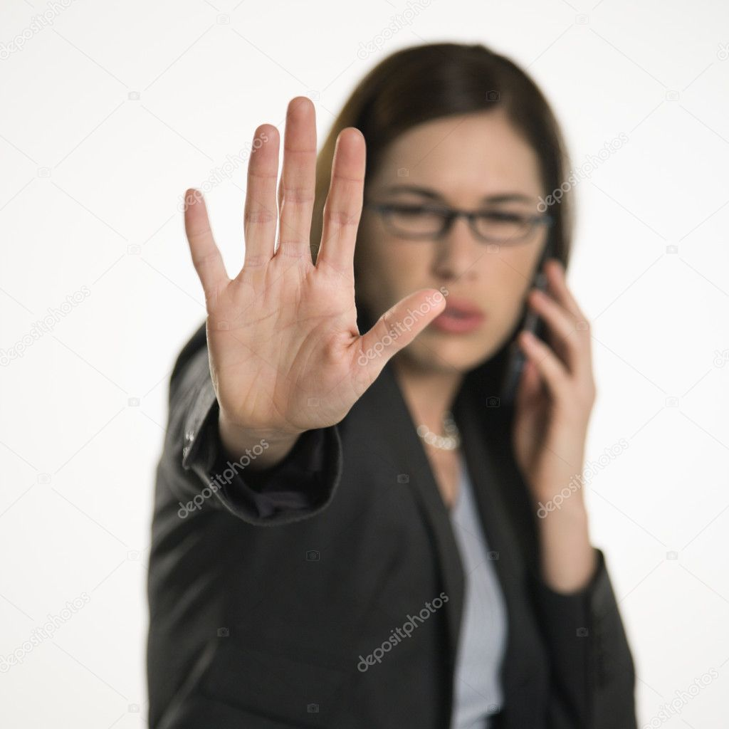 Caucasian mid adult professional business woman talking on cell phone holding hand out to stop viewer. viewer. — Stock Photo #9552529