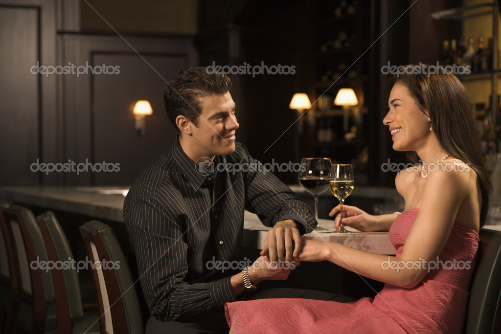 Mid adult Caucasian couple at bar holding hands and smiling.  Stock Photo #9553173