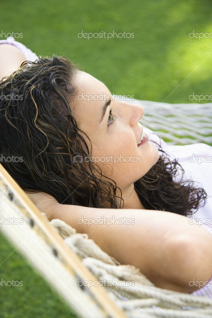 Side view of pretty young adult Caucasian brunette female lying in hammock smiling. — Stock Photo #9554215