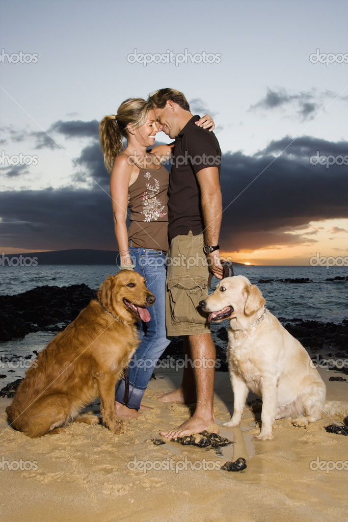 A man and woman hold the leashes of their dogs as they hug at a beach. Vertical format. — Stock Photo #9554350