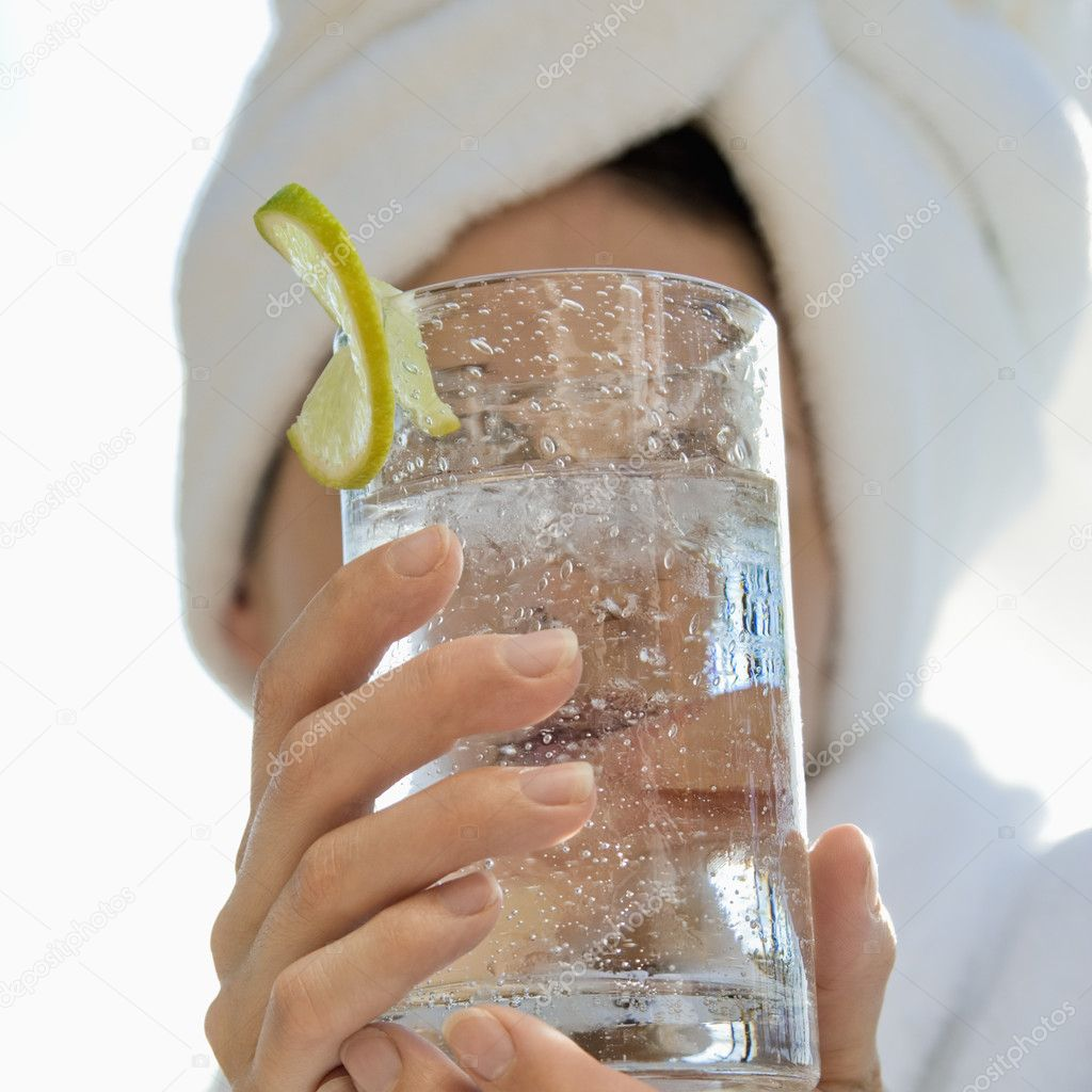 Caucasian mid-adult woman with towel on head holding drink glass with lime slice in front of face. — Stock Photo #9554427