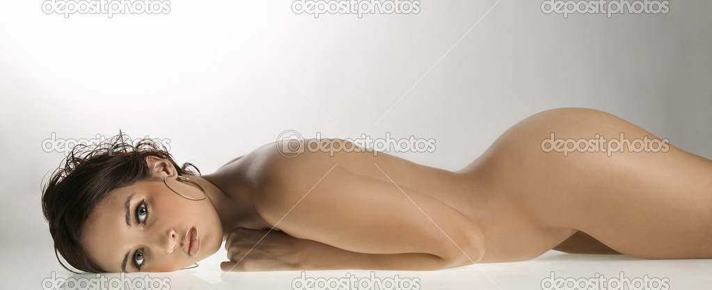 Nude Caucasian young adult woman lying on stomach looking at viewer.