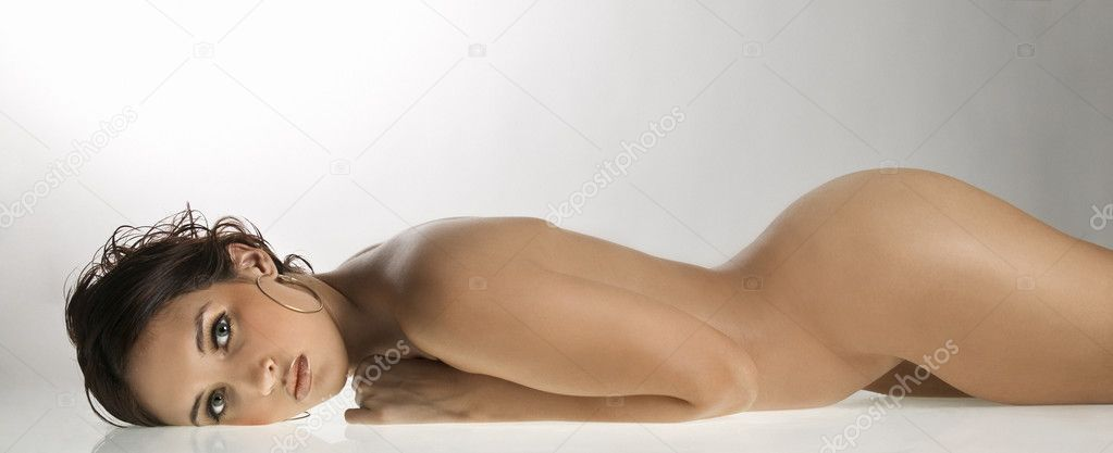 Nude Caucasian young adult woman lying on stomach  looking at viewer.  Stock Photo #9613437