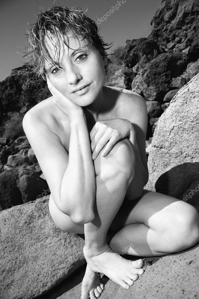 Mid adult nude Caucasian woman crouching on rock looking at viewer. — Stock Photo #9613672