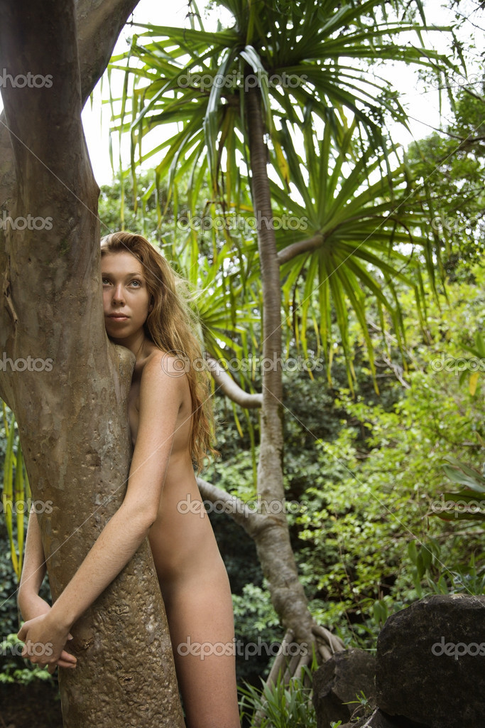 Nude Caucasian young adult woman in lush forest hugging tree. — Stock Photo #9614247