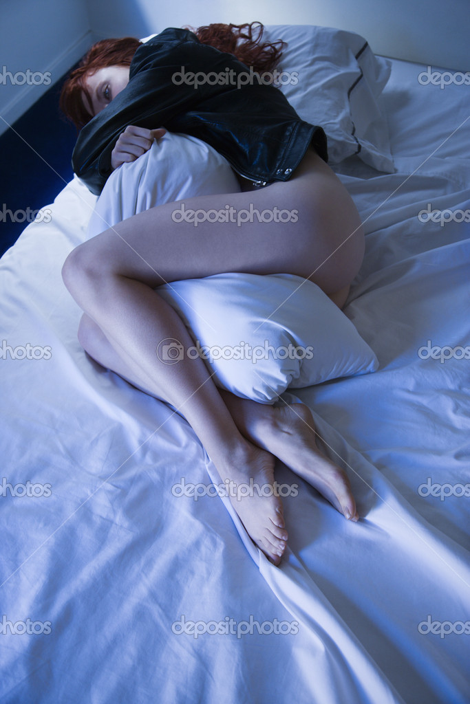 Partially nude young redhead woman lying in bed hugging pillow. — Stock Photo #9614534