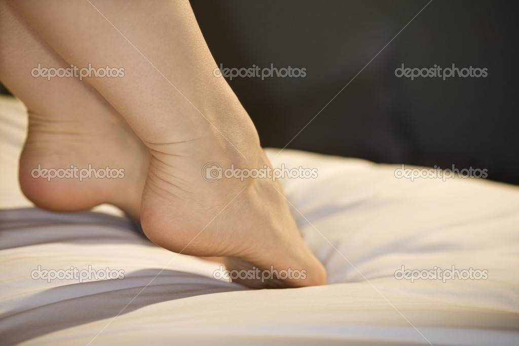 Close up of young Caucasian womans outstretched feet on bed.  Stock Photo #9614904