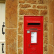 Red british post box on stone wall — Stock Photo