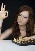 Young woman playing chess at home — Stok fotoğraf
