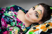 Young happy girl lying with beautiful make up on her face — Stock Photo