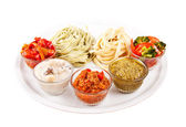 Two italian tagliatelles and five various condiments — Stock Photo