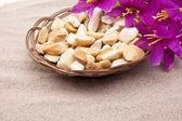 Stones with flowers on beach — Stock Photo
