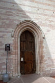 The side access door of the church in Assisi — Stock Photo