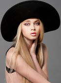 Fashion teen model in a black big hat in studio — Stock Photo