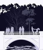 Mladí pěšky přes most v parku — Stock fotografie