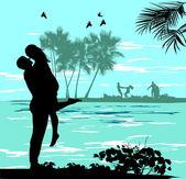 Mann hält eine frau am strand nahe dem meer — Stockfoto
