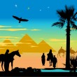 Travelers around the pyramids and palm-trees at night — Stock Photo