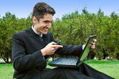 Young man with cell phones and laptop. — Stock Photo