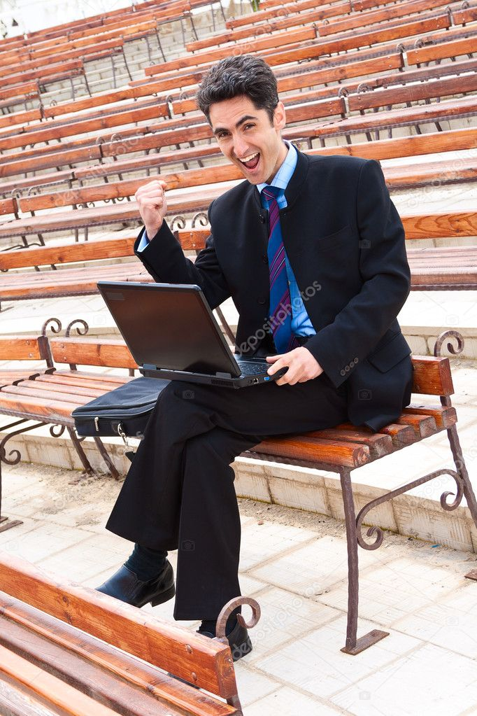Young man is working on laptop on the bench. — Stock Photo #10197501