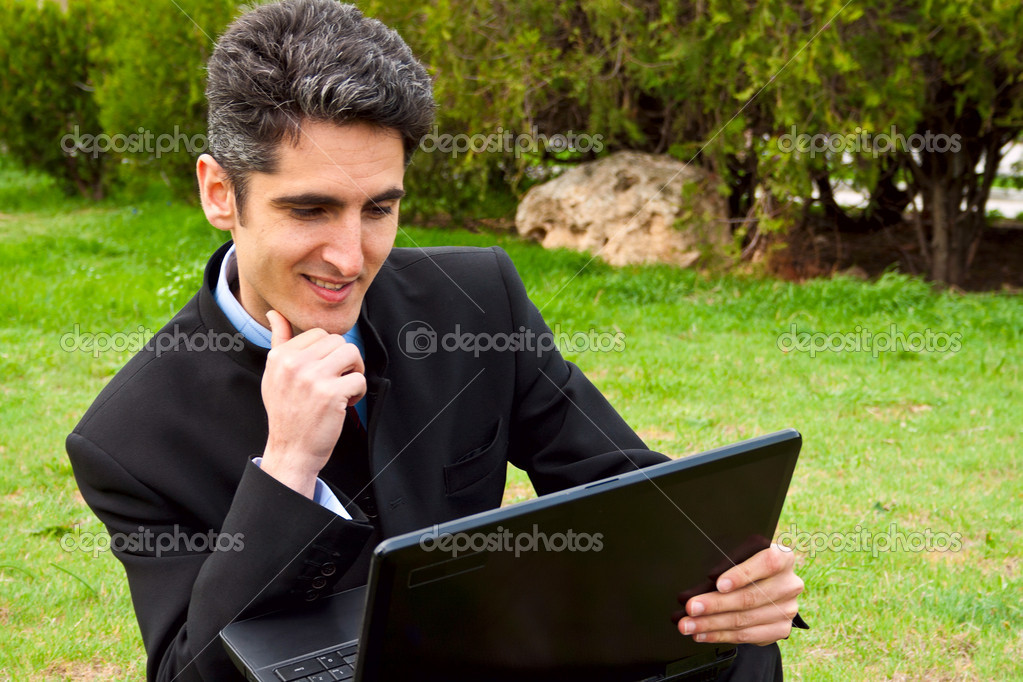 Young man is working on laptop in the park — Stock Photo #10243233