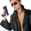 Handsome man with gun in leather raincoat — Stock Photo