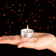 Candle with many-colored sparkles on hand. — Zdjęcie stockowe