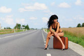 Brunette with suitcase in road, highway. — Stock Photo