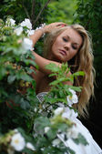 Sexy Blonde Peering Over Roses — Stock Photo