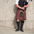 Bagpiper dressed in kilt playing bag pipes — Stock Photo