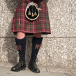 Bagpiper dressed in kilt playing bag pipes - Stockfoto