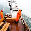 Wearing orange coats on fishing boat — Stock Photo #9283136