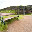 Stock Photo: Bench for resting near waterfall